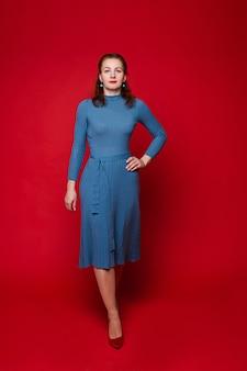 Ładna kaukaska kobieta w niebieskiej sukience i czerwonych butach z bladą skórą pokazuje różne pozy do kamery
