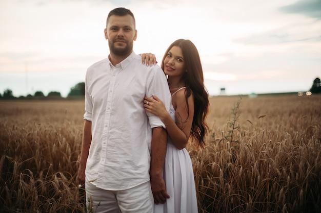Ładna kaukaska kobieta z długimi ciemnymi falującymi włosami w białej sukni przytula się z pięknym mężczyzną w białej koszulce i szortach