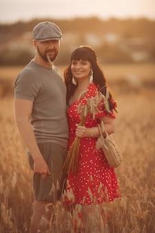 Ładna kaukaska kobieta z długimi ciemnymi falującymi włosami w czerwonej sukience z torbą i kwiatami przytula się ze swoim pięknym chłopakiem w szarej koszulce, kapeluszu i szortach