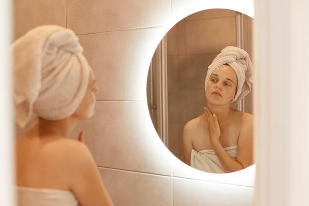 Ładna kaukaska kobieta z ręcznikiem na głowie, dotykając szyi w łazience, patrząc na swoje odbicie w lustrze, wykonując zabiegi kosmetyczne i higieniczne po wzięciu prysznica.