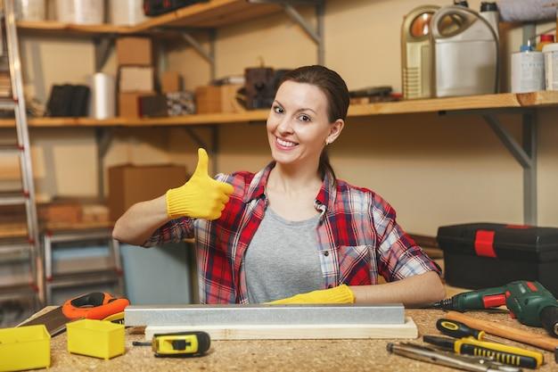 Ładna kaukaska młoda kobieta o brązowych włosach w koszuli w kratę, szarej koszulce, żółtych rękawiczkach, pokazując kciuk do góry, pracująca w warsztacie stolarskim przy drewnianym stole z kawałkiem żelaza i drewna, różne narzędzia
