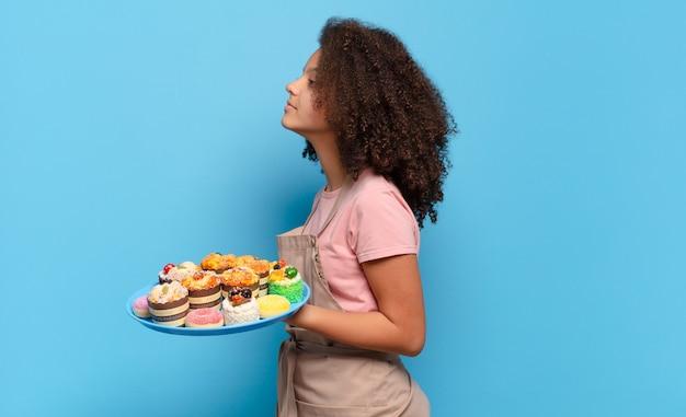 Ładna kobieta afro w widoku profilu, która chce skopiować przestrzeń do przodu, myśleć, wyobrażać sobie lub marzyć. humorystyczny koncepcja piekarza
