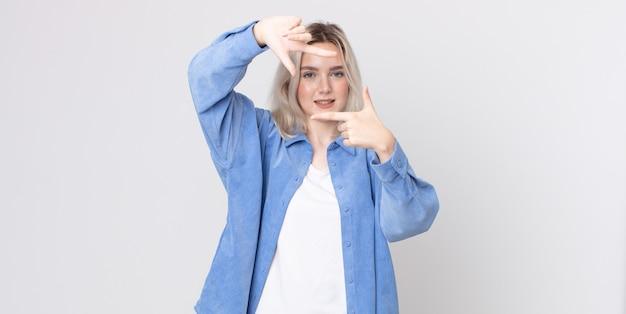 Ładna kobieta albinos czuje się szczęśliwa, przyjazna i pozytywna, uśmiechając się i robiąc portret lub ramkę na zdjęcia rękoma