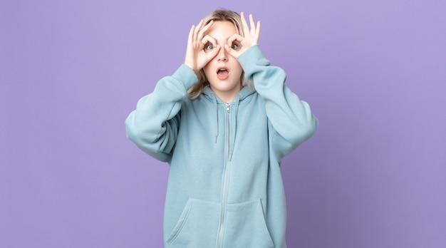 Ładna kobieta albinos czuje się zszokowana, zdumiona i zaskoczona, trzymając okulary ze zdziwionym, niedowierzającym spojrzeniem