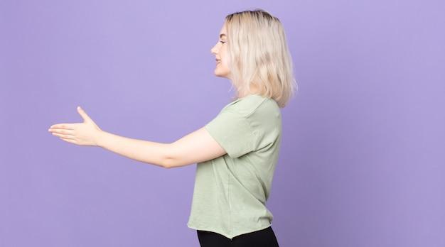 Ładna kobieta albinos uśmiechająca się, witająca cię i oferująca uścisk dłoni, aby zamknąć udaną transakcję, koncepcja współpracy