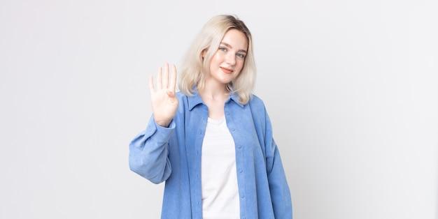 Ładna kobieta albinos uśmiechnięta i wyglądająca przyjaźnie, pokazująca cyfrę cztery lub czwartą z ręką do przodu, odliczającą w dół