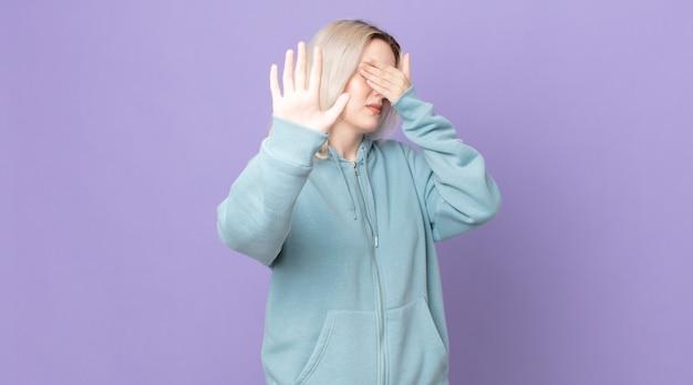 Ładna kobieta albinos zakrywająca twarz dłonią i kładąca drugą rękę do przodu, aby zatrzymać aparat, odmawiając robienia zdjęć lub zdjęć