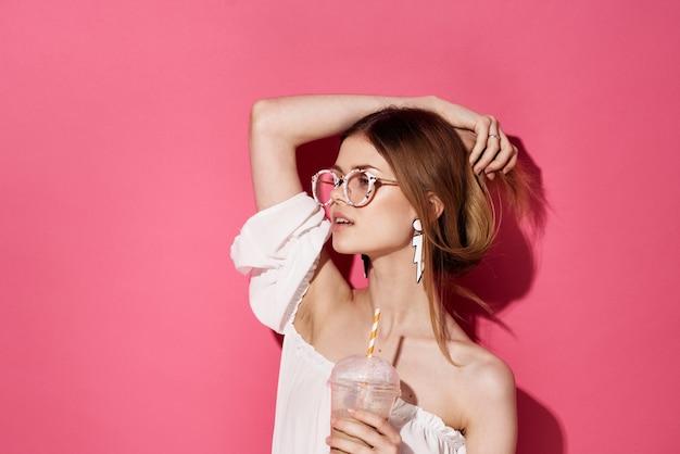 Ładna kobieta atrakcyjny wygląd pić w rękach nastolatek urok różowe tło. wysokiej jakości zdjęcie