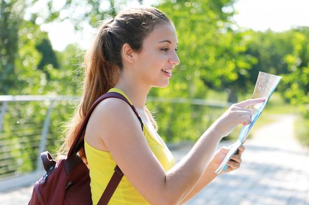 Ładna kobieta backpacker palcem wskazującym lokalizację na mapie
