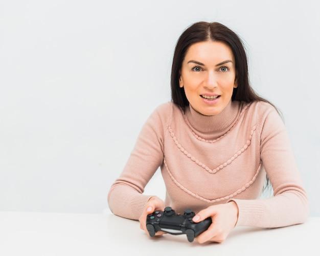 Ładna kobieta bawić się gemową konsolę przy stołem
