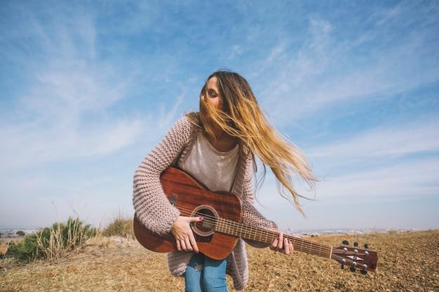 Ładna kobieta bawić się gitarę w polu