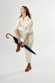 Ładna kobieta biały kombinezon parasol w ręce zgięte nogi w studio kolana