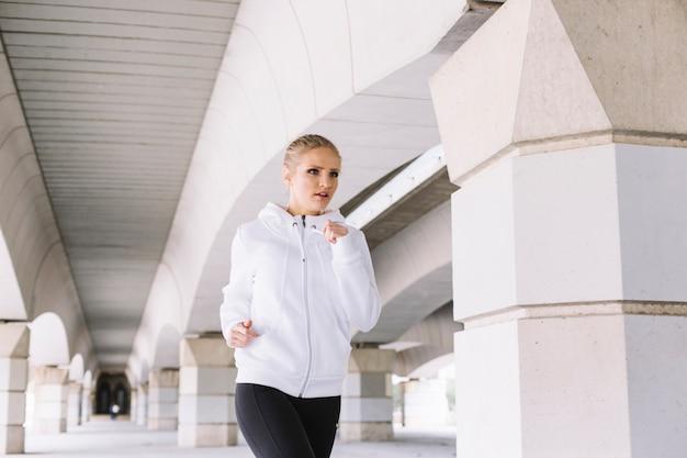 Ładna kobieta biega blisko filarów