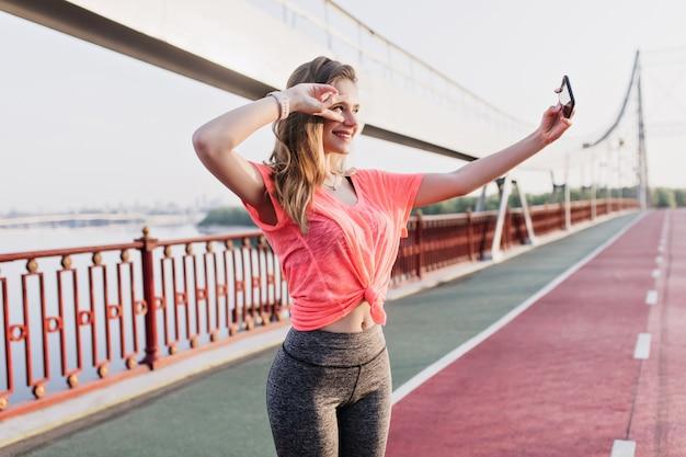 Ładna kobieta biegacz za pomocą smartfona do selfie na torze żużlowym. zmysłowa dziewczyna w strojach sportowych robi sobie zdjęcia.