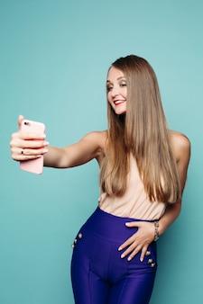 Ładna kobieta bierze selfie przez telefonu komórkowego nad zielonym tłem.