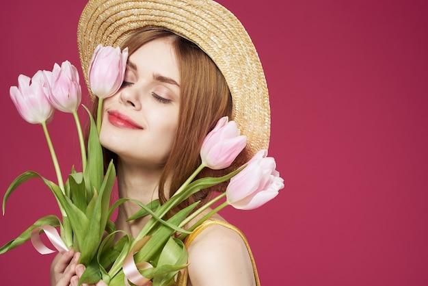 Ładna kobieta bukiet kwiatów wakacje dzień kobiet różowe tło. wysokiej jakości zdjęcie