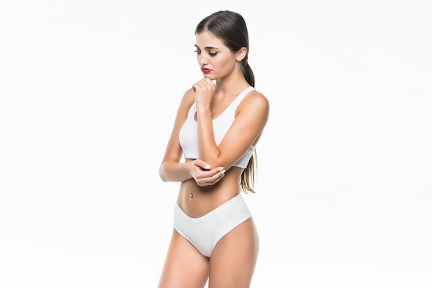 Ładna kobieta cierpi na ból łokcia na białym tle na białej ścianie