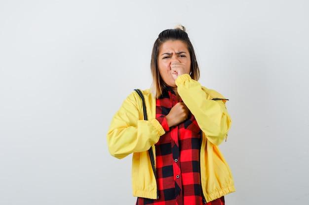 Ładna kobieta cierpi na kaszel w koszuli, kurtce i patrząc chory, widok z przodu.