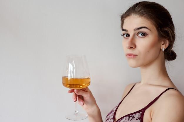 Ładna kobieta, ciesząc się lampką białego wina