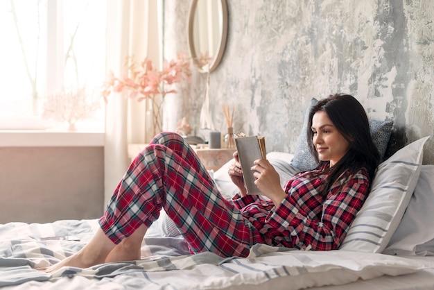 Ładna kobieta cieszy się czytelniczą książkę w łóżku