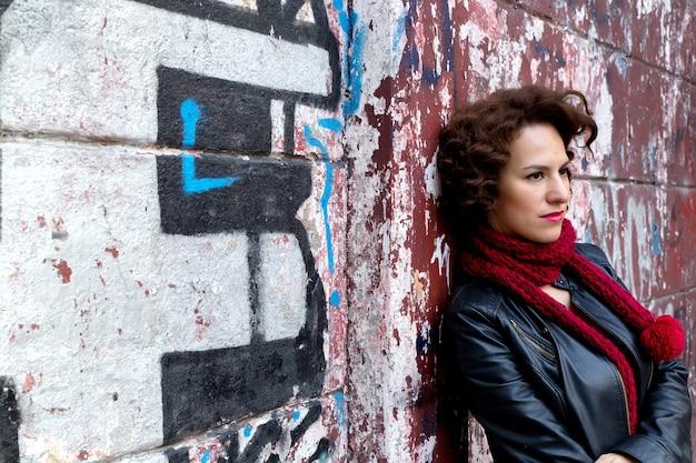 Ładna kobieta czeka przy graffiti ścianą