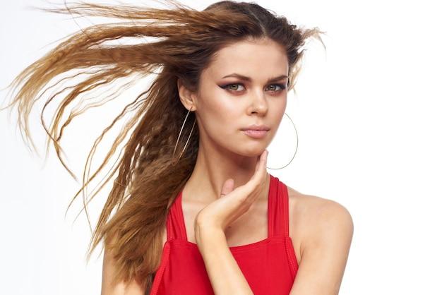Ładna kobieta czerwony podkoszulek falowane włosy atrakcyjny wygląd hotelu styl życia jasnym tle.
