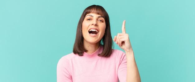 Ładna kobieta czując się jak szczęśliwy i podekscytowany geniusz po zrealizowaniu pomysłu, radośnie podnosząc palec, eureko!
