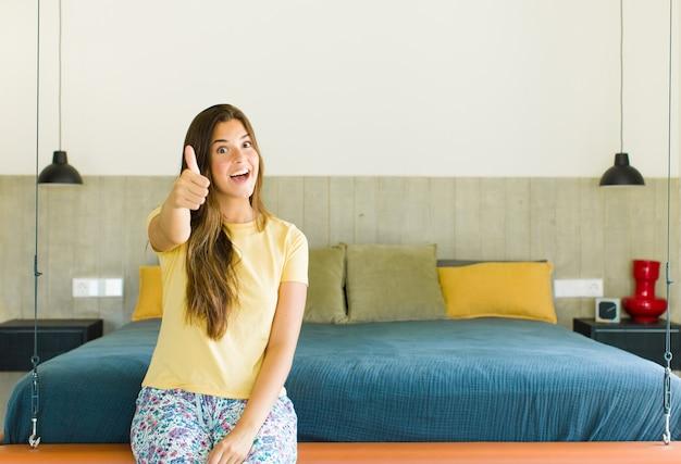 Ładna kobieta czująca się dumna, beztroska, pewna siebie i szczęśliwa, uśmiechająca się pozytywnie z kciukami do góry