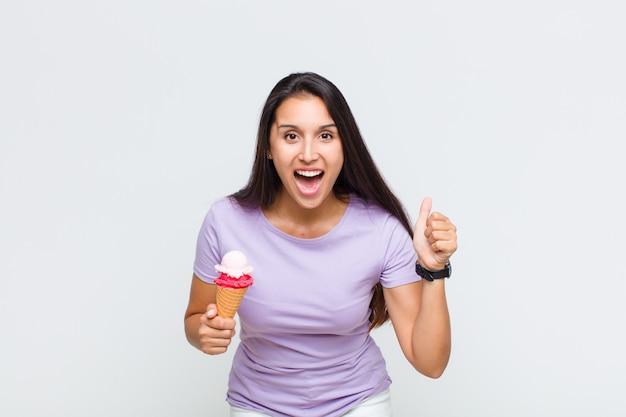 Ładna kobieta czująca się zszokowana, podekscytowana i szczęśliwa, śmiejąca się i świętująca sukces, mówiąca wow!