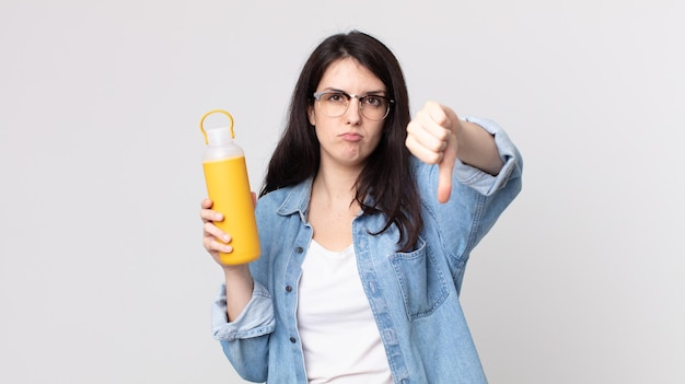 Ładna kobieta czuje krzyż, pokazuje kciuk w dół i trzyma termos z kawą