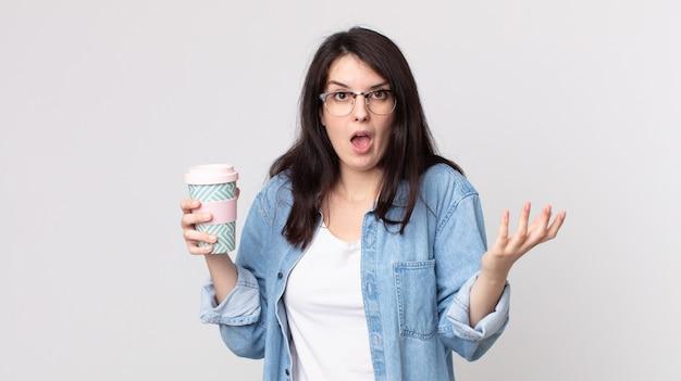 Ładna kobieta czuje się bardzo zszokowana i zaskoczona i trzyma kawę na wynos