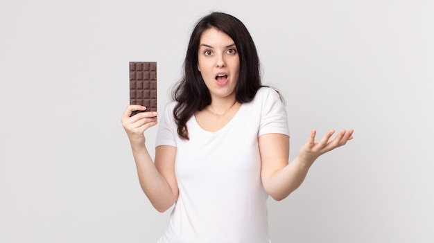 Ładna kobieta czuje się bardzo zszokowana i zaskoczona i trzyma tabliczkę czekolady