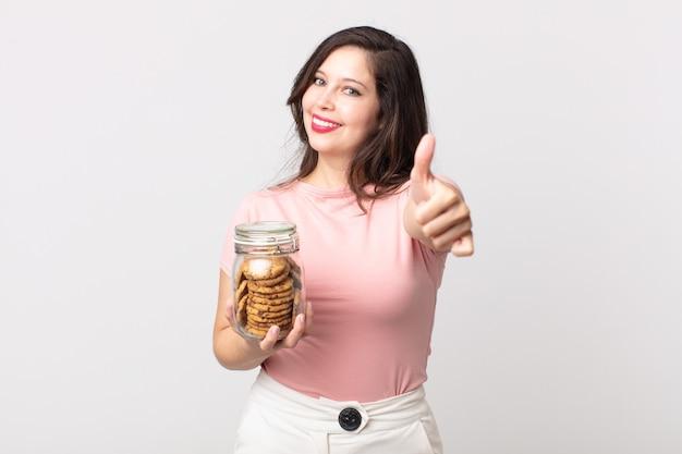 Ładna kobieta czuje się dumna, uśmiecha się pozytywnie z kciukami do góry i trzyma szklaną butelkę po ciastkach