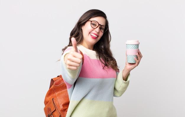 Ładna kobieta czuje się dumna, uśmiecha się pozytywnie z kciukami do góry. koncepcja studenta