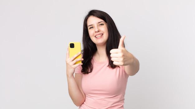 Ładna kobieta czuje się dumna, uśmiecha się pozytywnie z kciukami do góry za pomocą smartfona