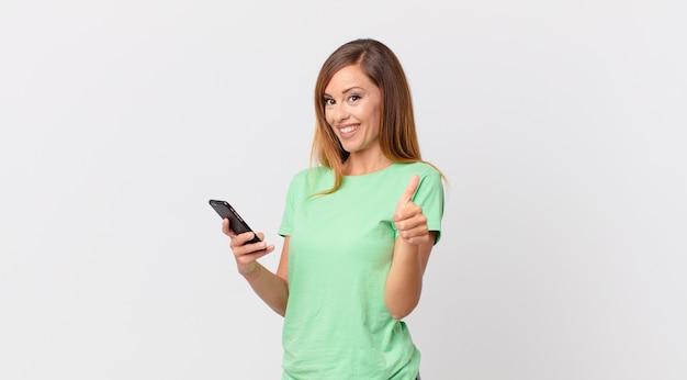 Ładna kobieta czuje się dumna, uśmiecha się pozytywnie z kciukami w górę i używa smartfona