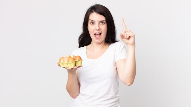 Ładna kobieta czuje się jak szczęśliwy i podekscytowany geniusz po zrealizowaniu pomysłu i trzymaniu pudełka z jajkami