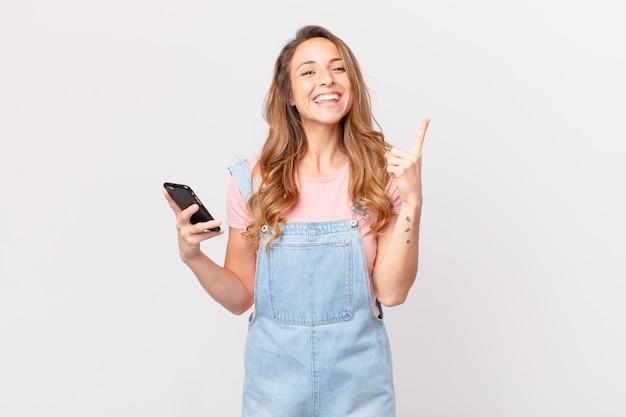 Ładna kobieta czuje się jak szczęśliwy i podekscytowany geniusz po zrealizowaniu pomysłu i trzymaniu smartfona
