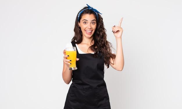 Ładna kobieta czuje się jak szczęśliwy i podekscytowany geniusz po zrealizowaniu pomysłu i trzymaniu szklanki soku pomarańczowego