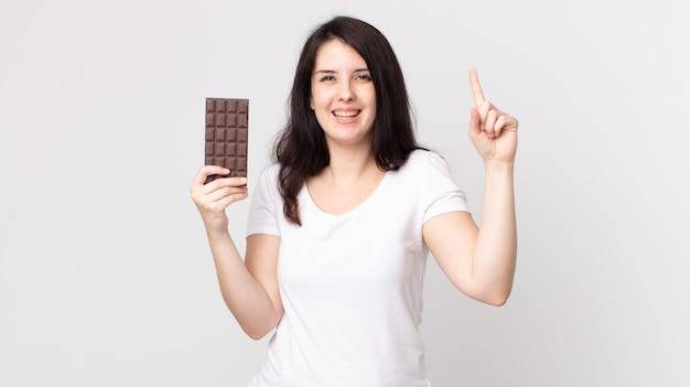 Ładna kobieta czuje się jak szczęśliwy i podekscytowany geniusz po zrealizowaniu pomysłu i trzymaniu tabliczki czekolady