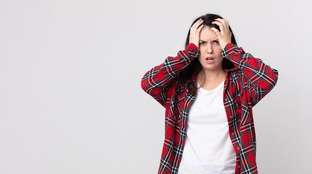 Ładna kobieta czuje się przerażona i wstrząśnięta, podnosi ręce do głowy i panikuje z powodu błędu