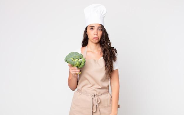 Ładna kobieta czuje się smutna i jęczy z nieszczęśliwym spojrzeniem i płacze w fartuchu i trzyma brokuły