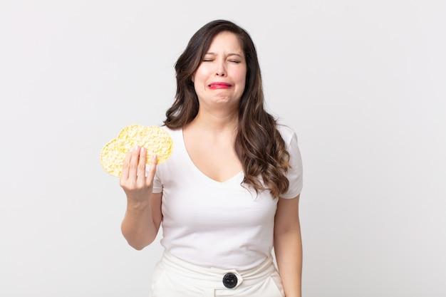 Ładna Kobieta Czuje Się Smutna I Marudna Z Nieszczęśliwym Spojrzeniem, Płacze I Trzyma Dietetyczne Ciastka Ryżowe Premium Zdjęcia