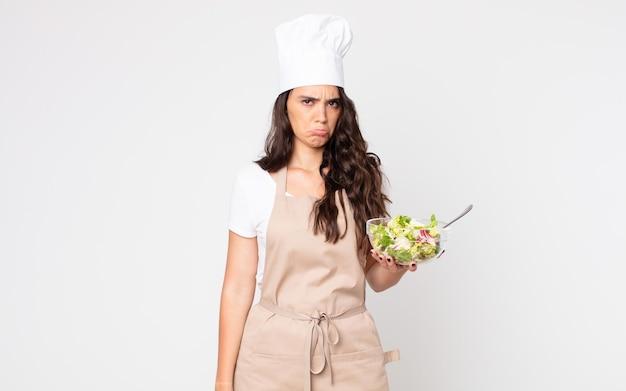 Ładna kobieta czuje się smutna, zdenerwowana lub zła i patrzy w bok, ubrana w fartuch i trzymająca sałatkę