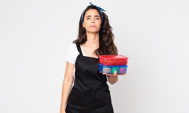 Ładna kobieta czuje się smutna, zdenerwowana lub zła, patrzy w bok i trzyma tupperware z jedzeniem