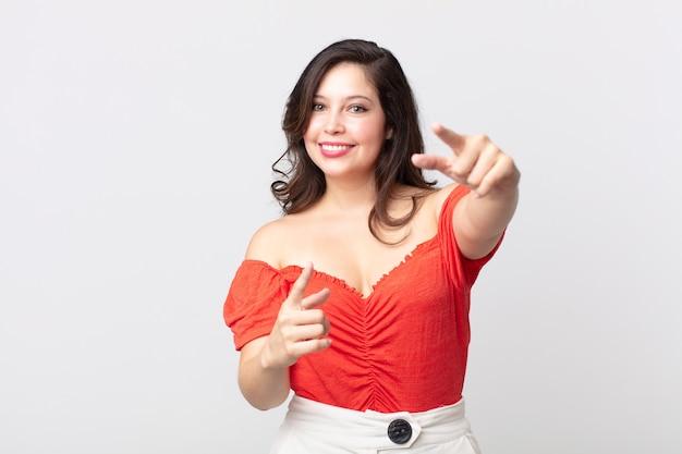 Ładna kobieta czuje się szczęśliwa i pewna siebie, wskazuje aparat obiema rękami i śmieje się, wybierając ciebie