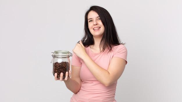 Ładna kobieta czuje się szczęśliwa i staje przed wyzwaniem lub świętuje i trzyma butelkę ziaren kawy