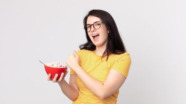 Ładna kobieta czuje się szczęśliwa i staje przed wyzwaniem lub świętuje i trzyma miskę śniadaniową