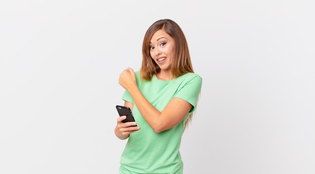 Ładna kobieta czuje się szczęśliwa i staje przed wyzwaniem lub świętuje i używa smartfona