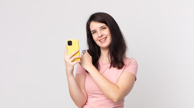 Ładna kobieta czuje się szczęśliwa i staje przed wyzwaniem lub świętuje za pomocą smartfona